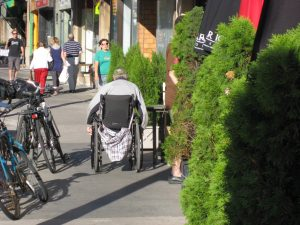 A picture of a senior navigating a crowded sidewalk on a wheelchair