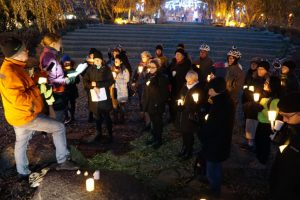 A picture of a vigil with people holding candles.