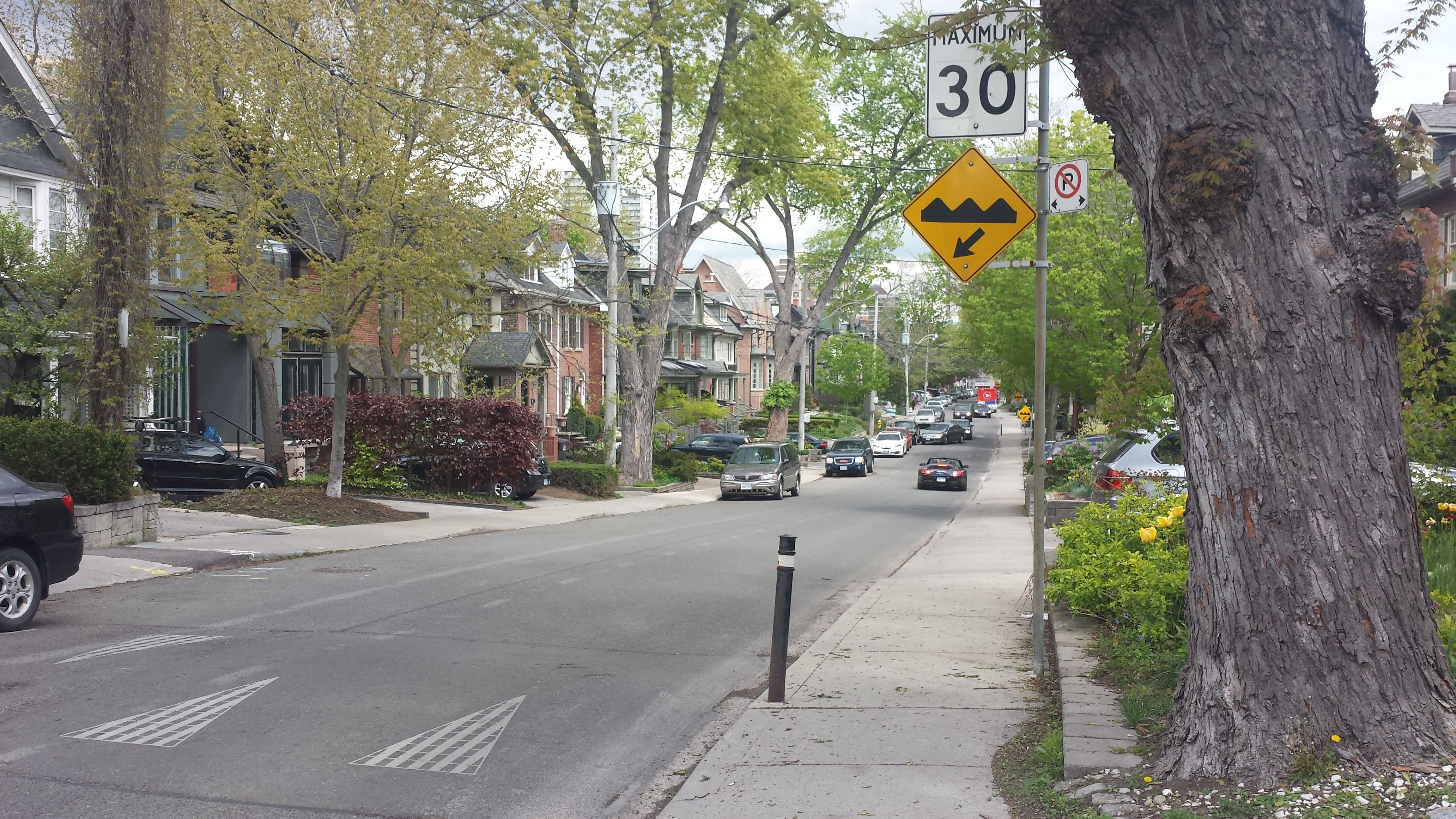 Picture of a residential street in Toronto with speed bumps and a sign that shows a speed limit of 30 kilometre per hour