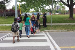 Children using a crosswalk on the way to school with the help of adults