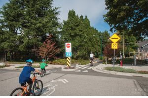 A picture of two boys on bikes entering a protected bike lane in a residential area