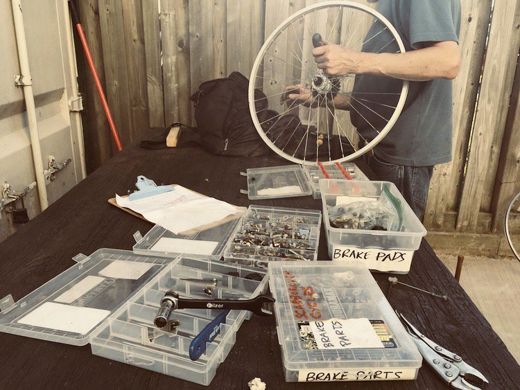 A table with bicycle repair parts and tools, and a person holding a bike wheel