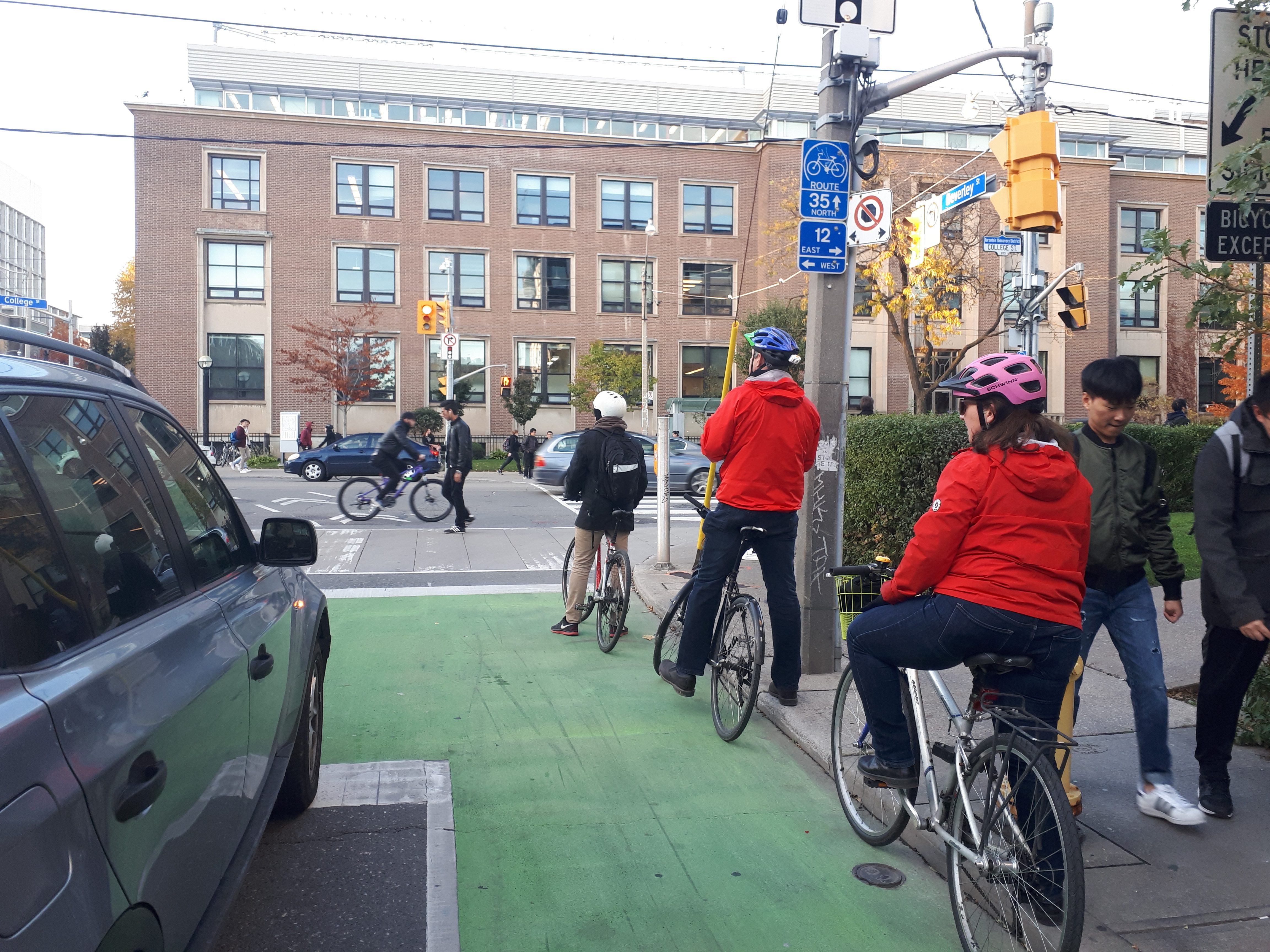 Three cyclists waiting at a light in a green painted bike box, with a car in the lane beside them.