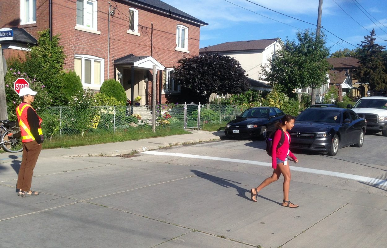 Child crossing the street, with crossing guard