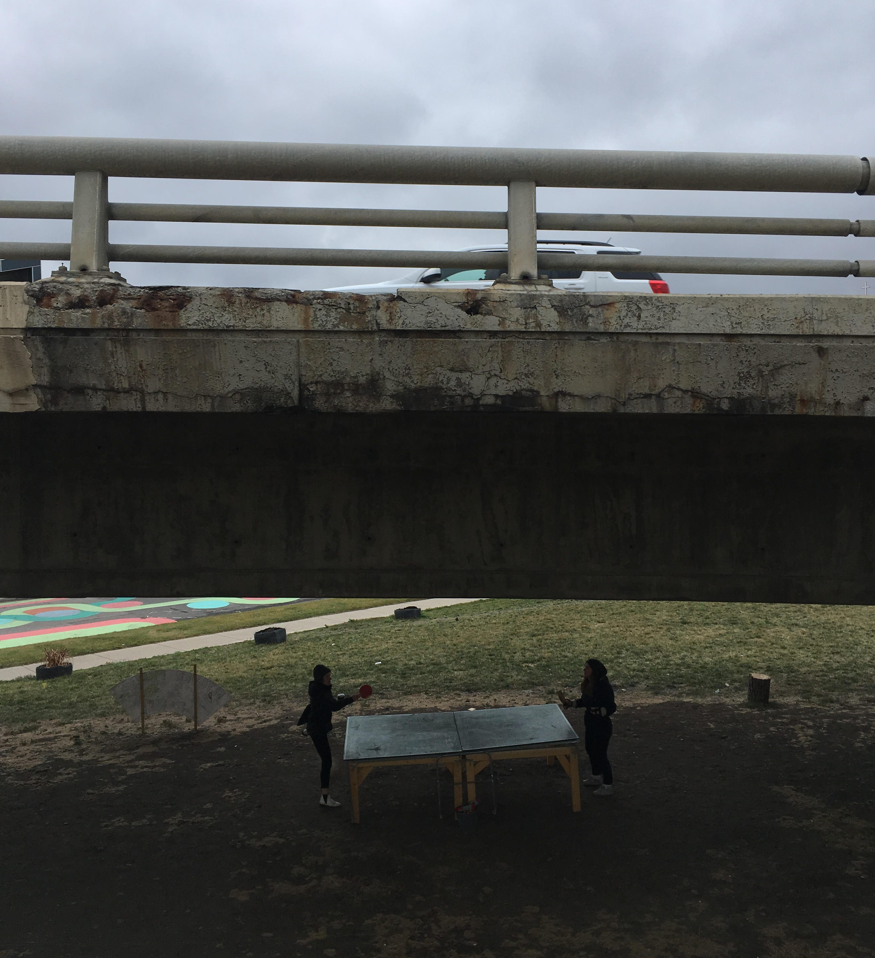 Two people playing ping pong under an elevated highway
