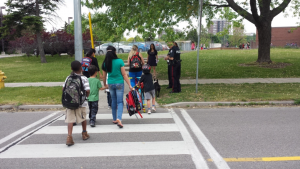 A picture of children using a crosswalk on the way to school with the help of adults.