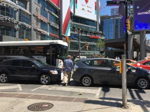 A picture of a man trying to cross a street using a crosswalk blocked by cars at Yonge and Dundas