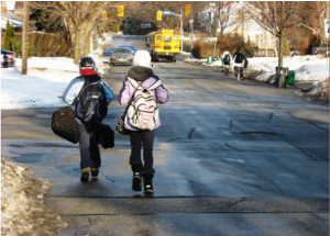 A picture of two children walking on a street without sidewalks on a snowy day.