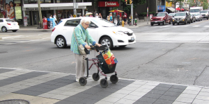 A picture of an old woman using a crosswalk with a mobility device