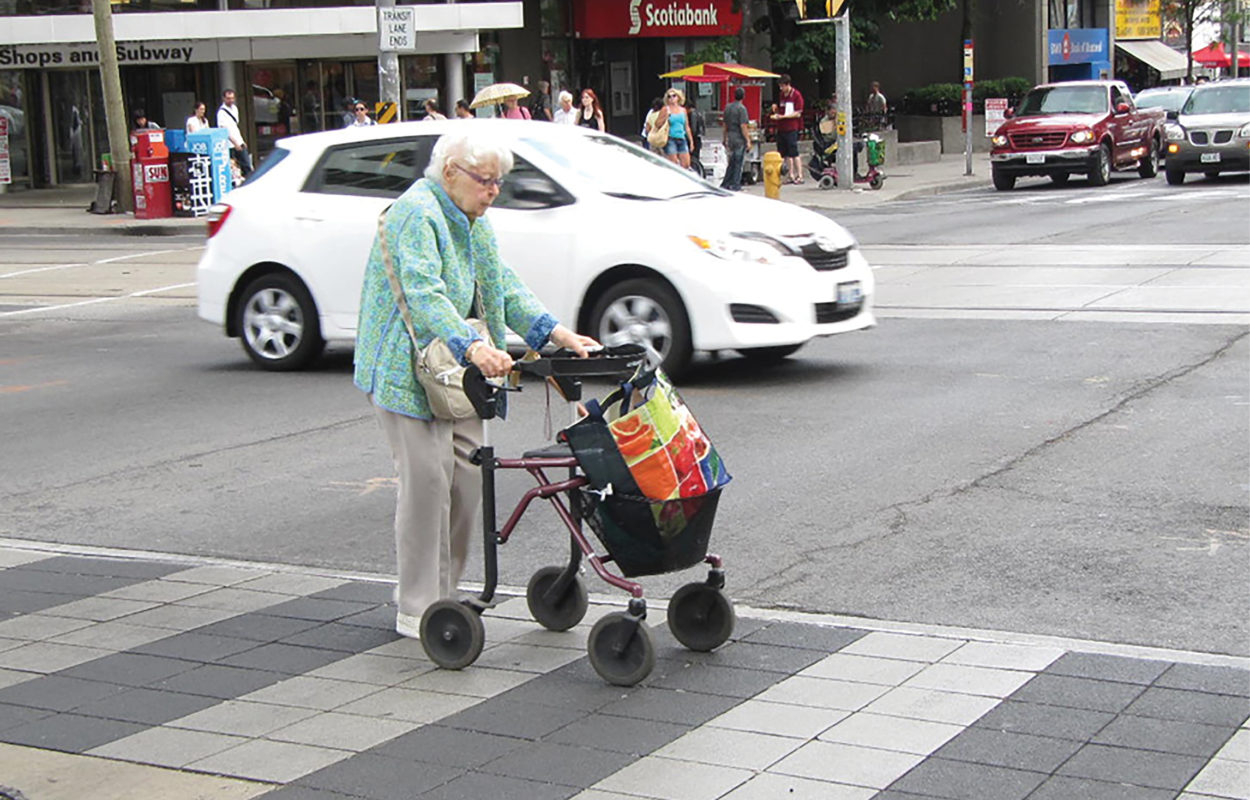 Senior with walker crossing the street in a crosswalk