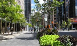 A picture of a rendering of a sidewalk that is wide and landscaped with people walking on it.