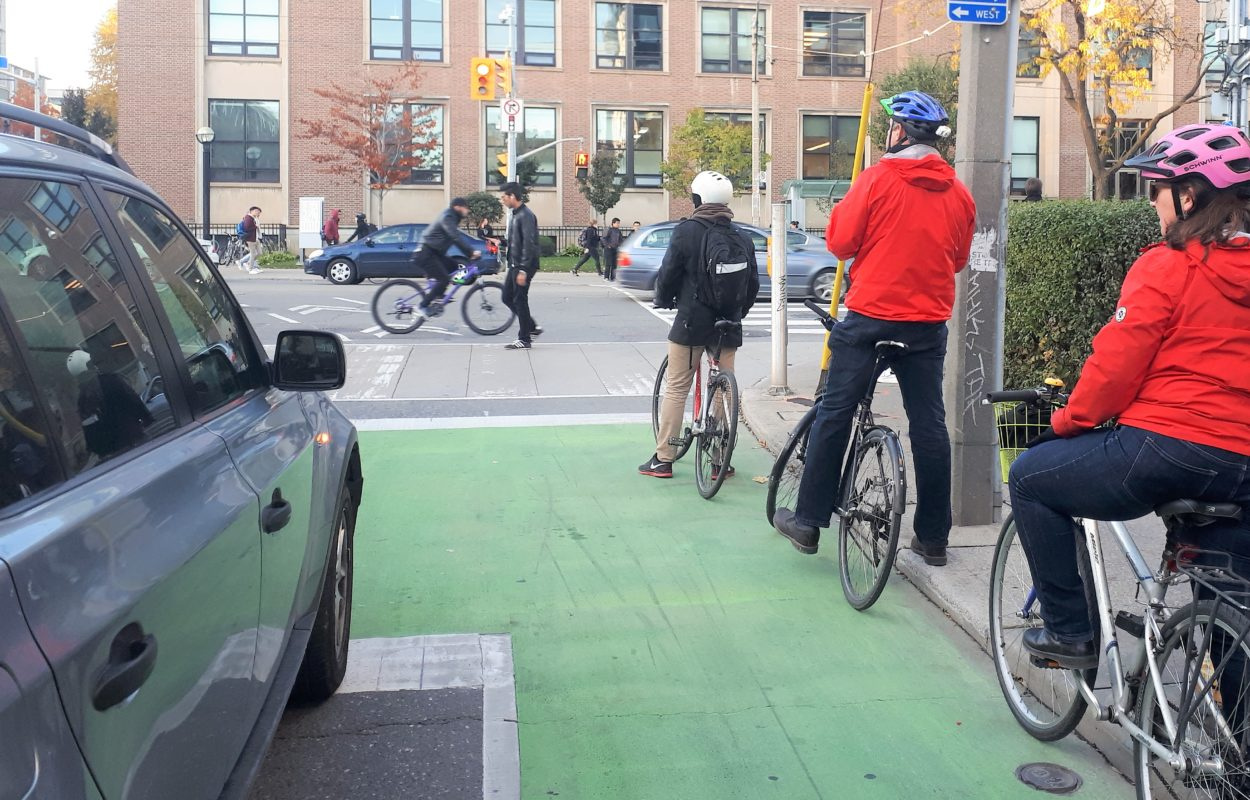 Three cyclists wait at a light in a green, painted bike box with a car beside them