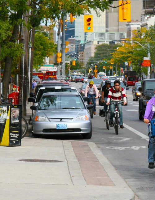 Cyclists, cars and public transit on College Street in Toronto