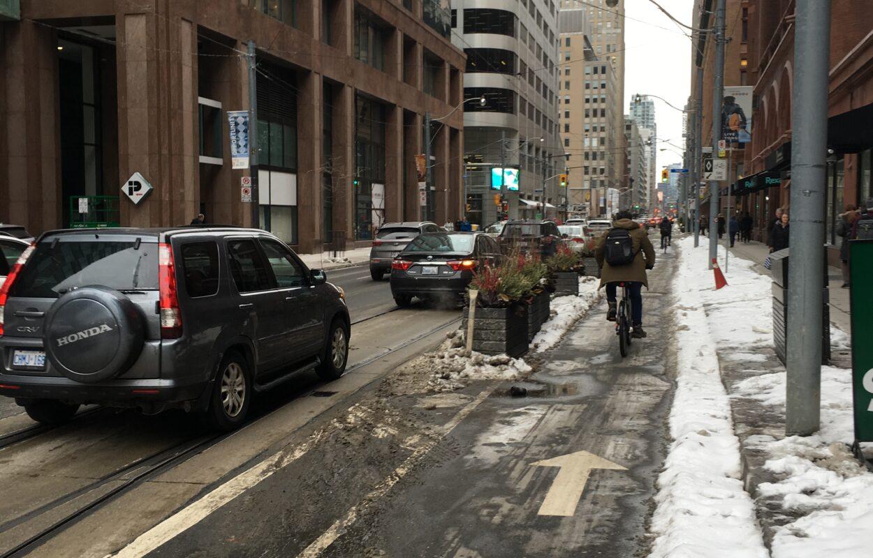 A cyclist biking down the Richmond Street bike lane in the winter