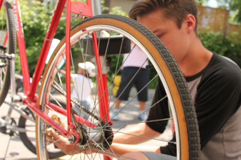 A person fixing a red bicycle