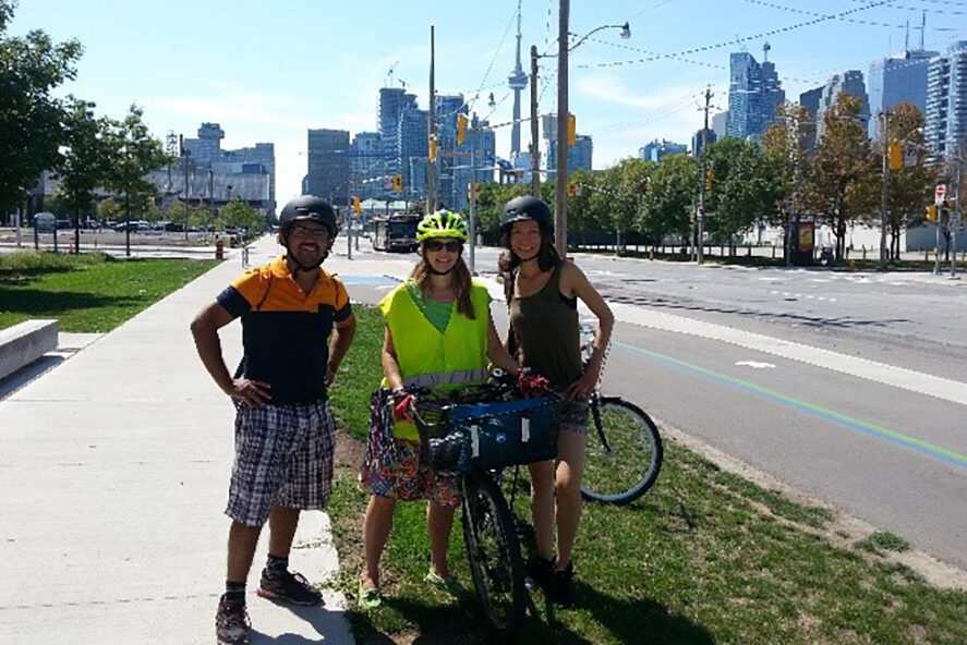 Picture of three people with helmets and bikes standing on a sidewalk next to a cycle lane.