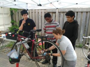Person fixing a bike while three others watch.